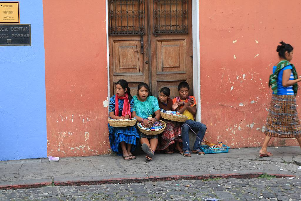 Kinder am Strassenrand in Antigua Guatemala, Vor orange-blauer Hauswand